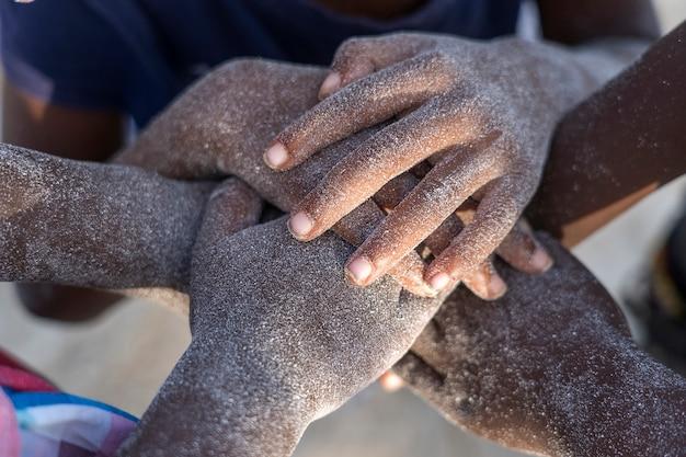 Viele afrikanische kinderhände, die auf sandstrand, tansania, afrika verbinden