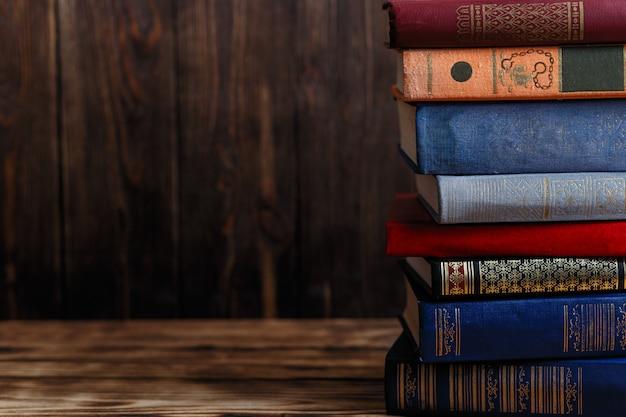 Viele alte bücher auf hölzernem hintergrund. die informationsquelle. buch drinnen öffnen. heimbibliothek. wissen ist macht