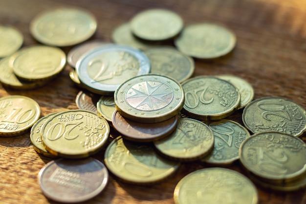 Viele alte rostige messing-euro-münzen auf einem hölzernen hintergrund