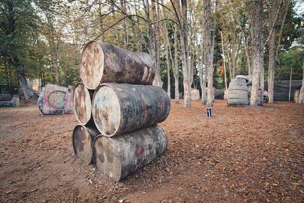 Viele alte runde fässer an der basis zum paintballspielen, hinter denen sich die vom spiel begeisterten spieler verstecken