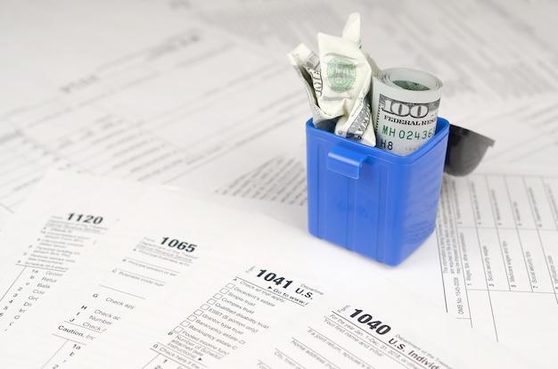 Viele amerikanischen steuerformulare und zerknitterten hundert dollaranmerkungen im abfalleimer
