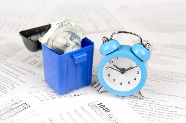 Viele amerikanischen steuerleerzeichen mit blauem wecker und zerknittertem hundert dollarschein im abfalleimer