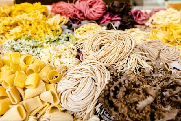 Viele arten von ungekochten italienischen nudeln in verschiedenen farben und formen
