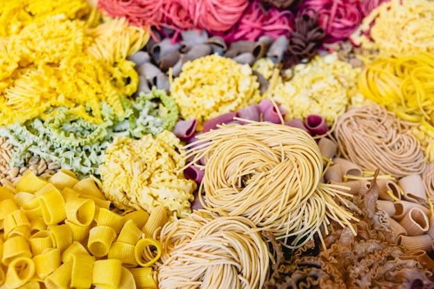 Viele arten von ungekochten italienischen teigwaren in verschiedenen farben und formen