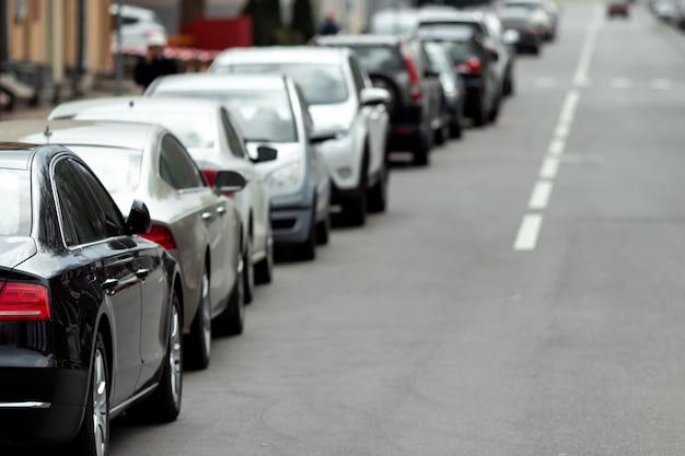 Viele autos parkten entlang der straße. mangel an, mangel an parkplätzen in großstädten.