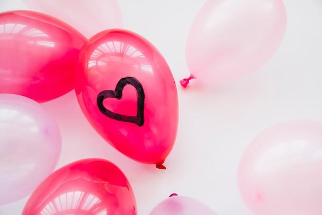Viele ballons mit bemaltem herzen