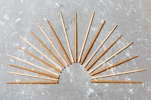 Viele bambusessstäbchen auf schwarzem zementstein