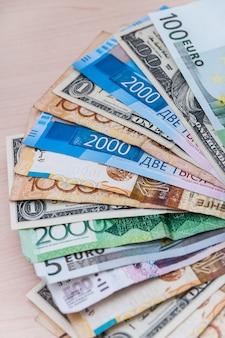 Viele banknoten aus verschiedenen ländern der welt, der wertunterschied ist auf dem tisch mit einem ventilator gestapelt.