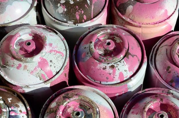 Viele benutzte rosafarbene metallbehälter mit farbe zum zeichnen von graffiti