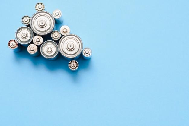 Viele benutzten aa-batterien auf blauem grund
