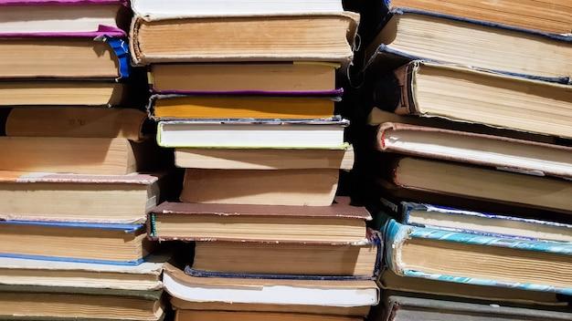 Viele benutzten alte bücher in der schulbibliothek. chaotisches layout von literaturstapeln, selektiver fokus. ein stapel bücher endet mit gestapeltem hintergrund. bücher in einer bibliothek - kulisse.