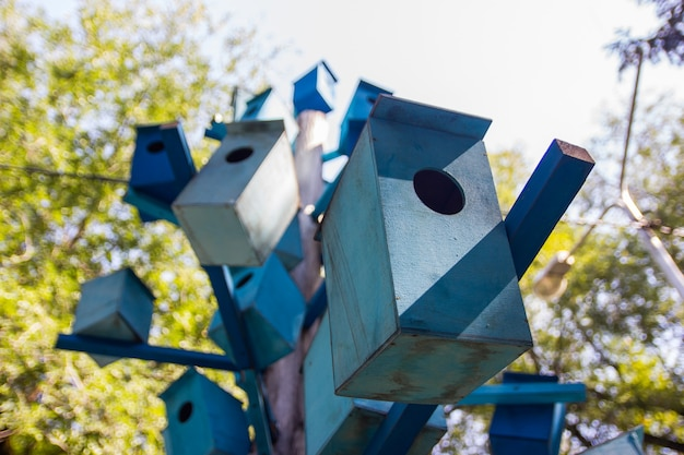 Viele blaue hölzerne vogelhäuschen auf einem baum eigentumswohnung konzept.