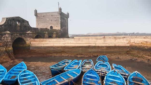 Viele blaue leere fischerboote nebeneinander gebunden