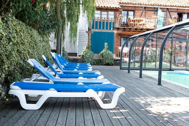 Viele blaue liegestühle neben dem pool