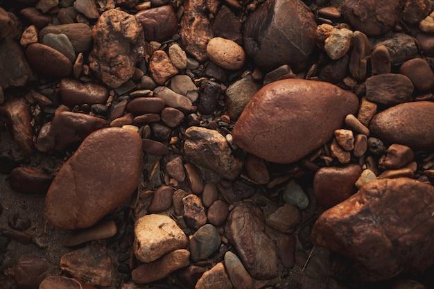 Viele braune runde kopfsteinpflastersteine mit verschiedenen formen und größen in den boden eingebettet. zenith-ansicht