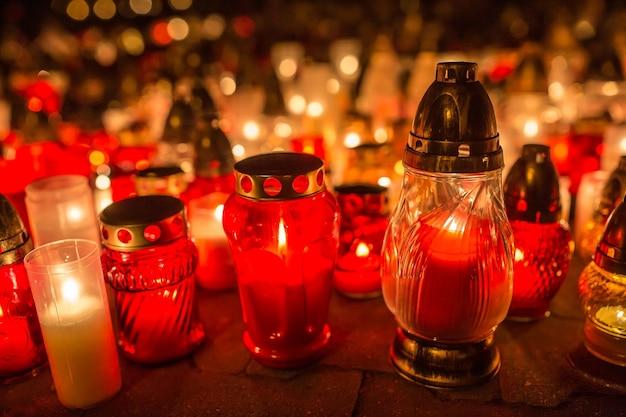 Viele brennende kerzen auf dem friedhof in der nacht anlässlich der seelen der verstorbenen.