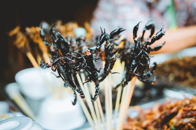 Viele brieten skorpion auf aufsteckspindeln an der yaowarat-straße in chinatown in bangkok, thailand.
