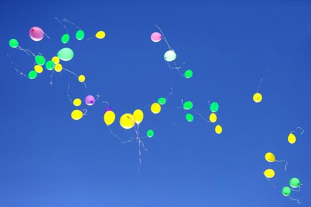 Viele bunte ballons fliegen in den blauen himmel. weihnachtsdekorationen