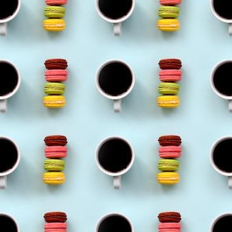 Viele bunte dessertkuchen makronen und kaffeetassen auf trendigen pastellblau