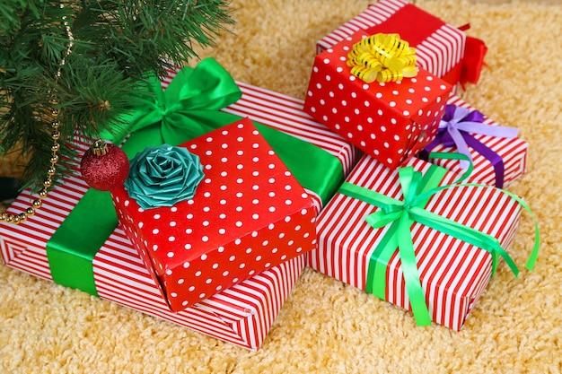 Viele bunte geschenke mit luxusbändern auf farbigem teppichhintergrund