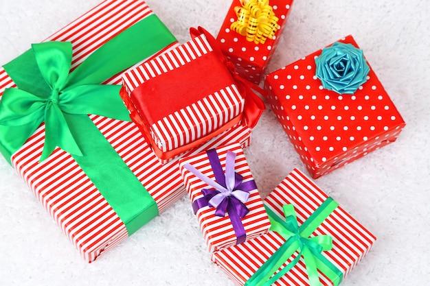 Viele bunte geschenke mit luxusbändern auf weißem hintergrund