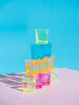 Viele bunte gläser auf einem weißen tisch, lokalisiert auf einem blauen hintergrund