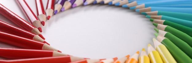 Viele bunte holzstifte, die in form eines kreises über den farben des regenbogennahaufnahmehintergrundes liegen