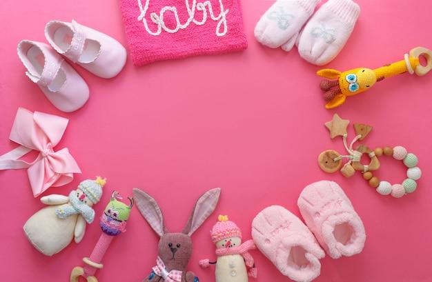 Viele bunte kinderspielzeuge, die auf einer rosa hintergrundoberansicht ausgelegt werden. platz für text