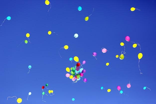 Viele bunte luftballons fliegen in den blauen himmel