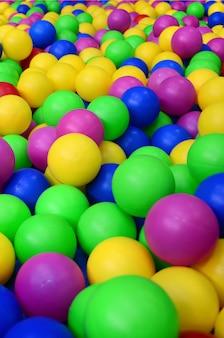 Viele bunte plastikkugeln in einem kinder-ballpit an einem spielplatz. muster schließen