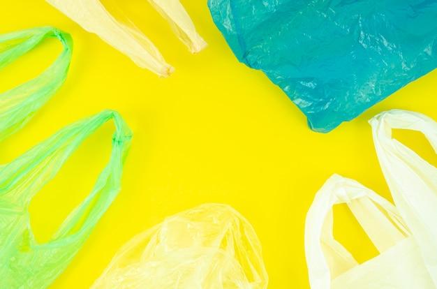 Viele bunte plastiktaschen auf gelbem hintergrund