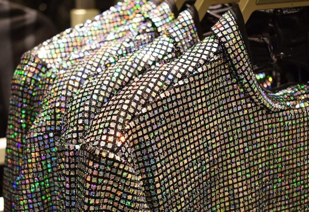 Viele bunte regenbogen-pailletten auf kleidern auf kleiderbügeln im laden trendige festliche kleidung für neujahr und weihnachten