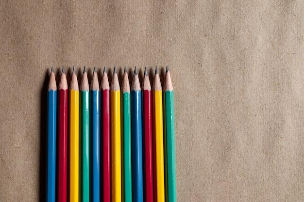Viele bunte stifte auf braunem papier können auf designs angewendet werden.