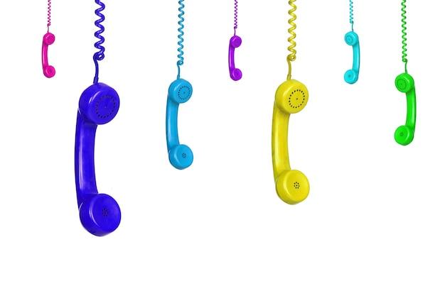 Viele bunte vintage-telefone, die isoliert auf weißem hintergrund hängen