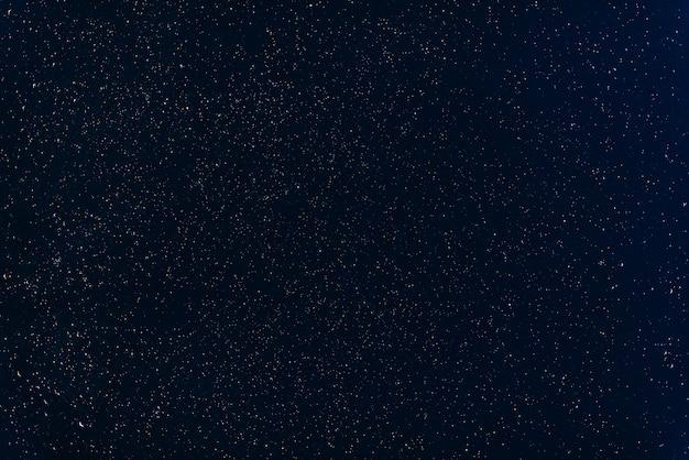Viele bunten sterne, die im dunkelblauen nachthimmel mit nebelflecken glänzen