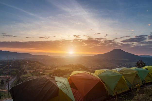 Viele campingzelt auf der grünen wiese nahe wald während des dramatischen sonnenaufgangs am nebligen sommermorgen, konzept des outdoor-campingabenteuers