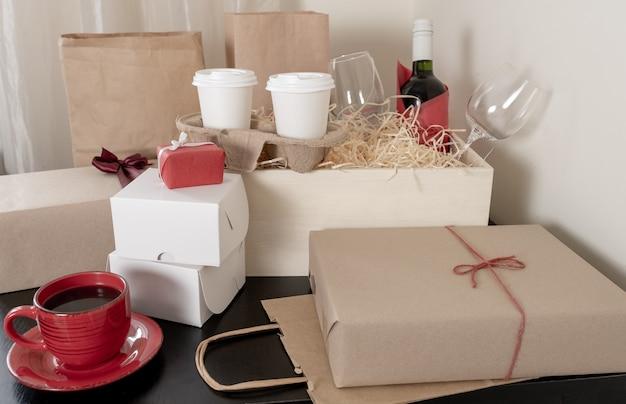 Viele craft paper taschen und schachteln, weinflasche und tassen kaffee auf dem tisch, lieferkonzept.