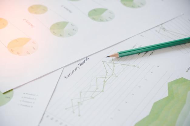 Viele diagramme und grafiken mit bleistift. reflexionslicht und aufflackern. konzeptbild des sammelns der daten und des statistischen arbeitens.