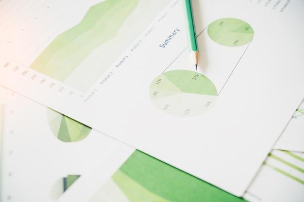 Viele diagramme und grafiken mit stift-bleistift. reflexionslicht und aufflackern. konzeptbild des sammelns der daten und des statistischen arbeitens.