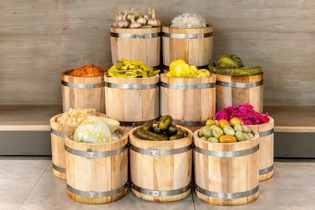 Viele eingelegtes gemüse in hölzernen eichenfässern seitenansicht bauernmarktkonzept