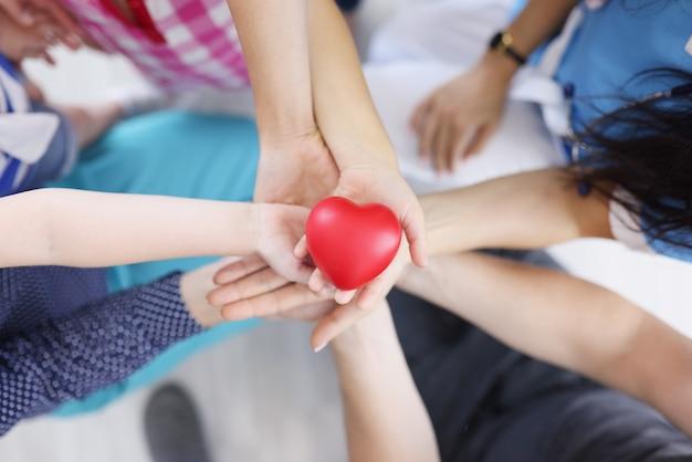 Viele erwachsene und kinderhände halten plastikspielzeugherz-draufsicht