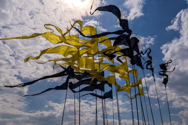 Viele fahnen an den fahnenmasten der gelben und schwarzen farben. fahnen in form von engen dreiecken