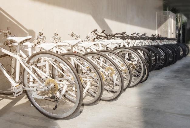 Viele fahrräder in einer reihe. schwarz-weiß-fahrräder stehen auf einem parkplatz für kunden.