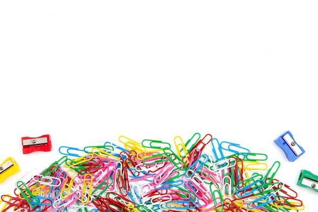 Viele farbige büroklammern und bleistiftspitzer auf einem weißen hintergrund. draufsicht und platz kopieren.
