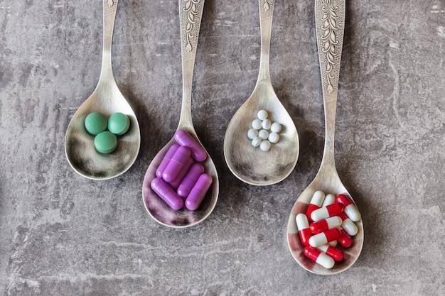 Viele farbige pillen und medikamente, vitamine, kapseln in einem löffel. konzept-apotheke, lebensmittelzusatzstoffe, missbrauch und drogenabhängigkeit, drogenabhängigkeit.