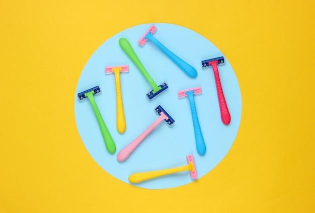 Viele farbige plastikrasierer auf gelbem hintergrund mit blauem pastellkreis. minimalistisches schönheitsstillleben