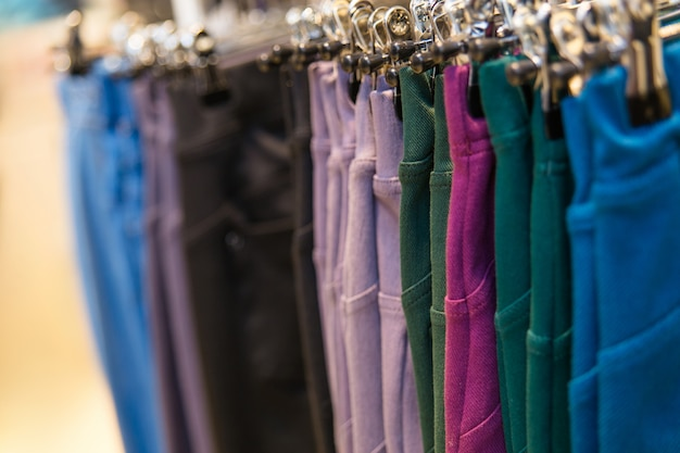 Viele farbigen denimhosen, die an den aufhängern in einem bekleidungsgeschäft hängen.