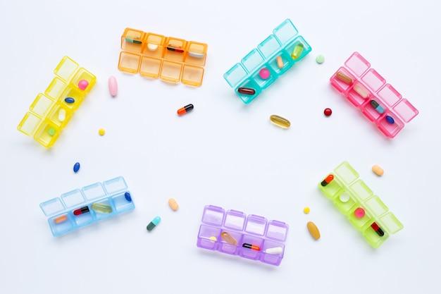 Viele farbigen tabletten und kapseln mit dem pillenkasten lokalisiert auf weiß