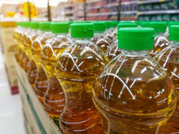Viele flaschen im reihenstapel pflanzenöl in den regalen im supermarktmaterial