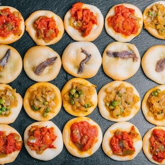 Viele frisch gebackene mini-pizzen. traditionelles spanisches gebäck mit gemüse.